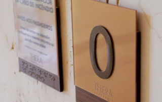 Placas de parede com braille e aviso de elevador